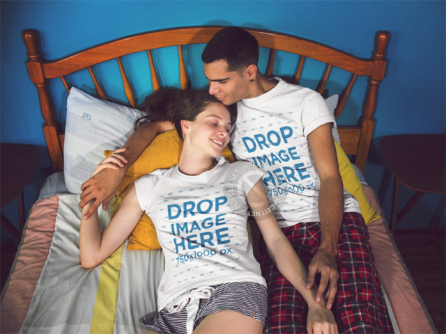 Two People Lying on a Bed and Holding Hands While Wearing Matching T-Shirts and Smiling Template a13454