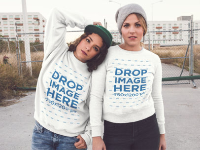 Two Girls Wearing Crewneck Sweatshirts With Matching Designs While Outside of the City Mockup a13343