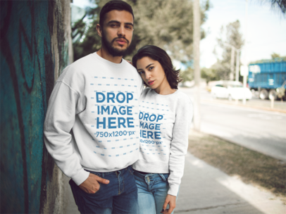 Hispanic Couple Wearing Matching Crewneck Sweatshirts While In The Street Mockup a13429