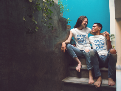 Mockup of a Couple Wearing Same Tees While Sitting in a Concrete Stairway With a Turquoise Wall a13489