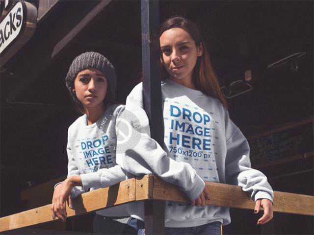 Pair of Girls Wearing Crewneck Sweatshirts With Matching Designs While in a Bar Mockup a13348