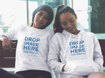 Two Girls Wearing a Crewneck Sweatshirt and a Pullover Hoodie While Sitting on a Bench Mockup a13349