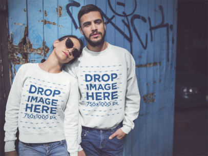 Young Hispanic Couple Being Cool While Wearing Matching Crewneck Sweatshirts Against a Blue Door Mockup a13426