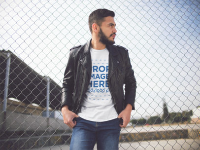 Young Hispanic Man Wearing a Leather Jacket on Top of a T-Shirt While Looking at an Industrial Area Outside of the City a13421