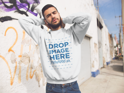 Mockup of an Hispanic Man Wearing a Crewneck Sweatshirt While Doing Faces in the Street a13423