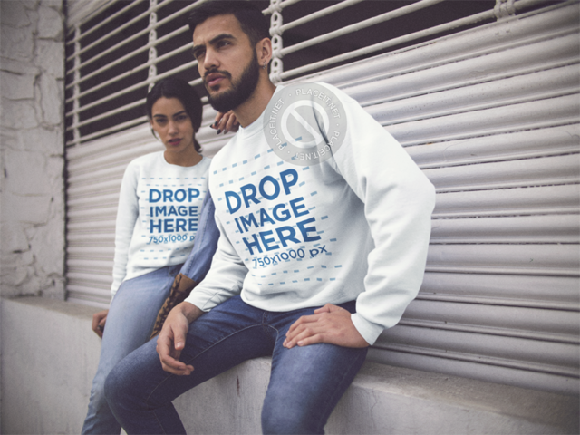 Young Couple Wearing Matching Crewneck Sweatshirts While Sitting Down in a Closed Store Entrance Template a13435