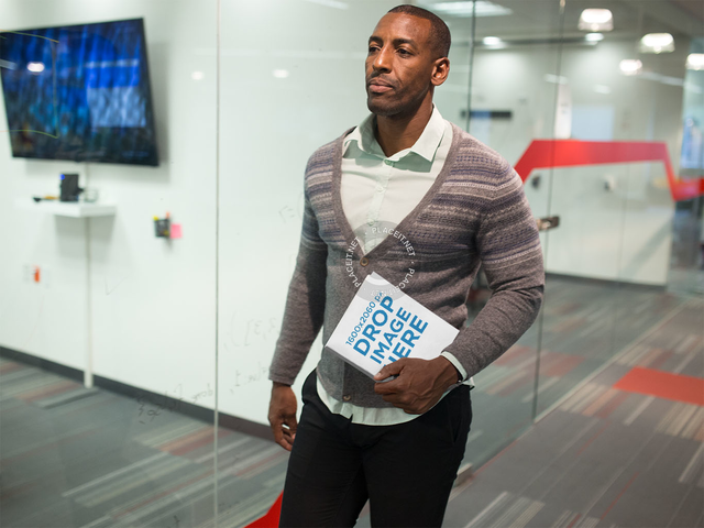 Black Man Holding a Book While Walking Through an Office Mockup a14509