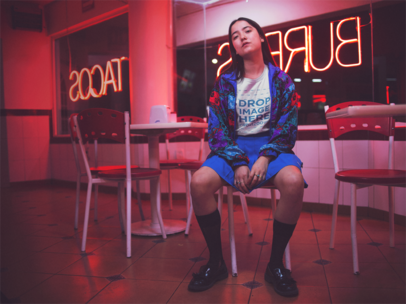Young Asian Girl Sitting Down While Wearing a Tshirt Inside a Mexican Restaurant at Night Mockup a13589
