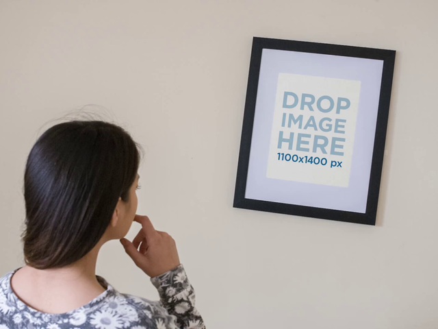 Young Girl Adjusting a Framed Art Print on her White Wall Mockup a14361