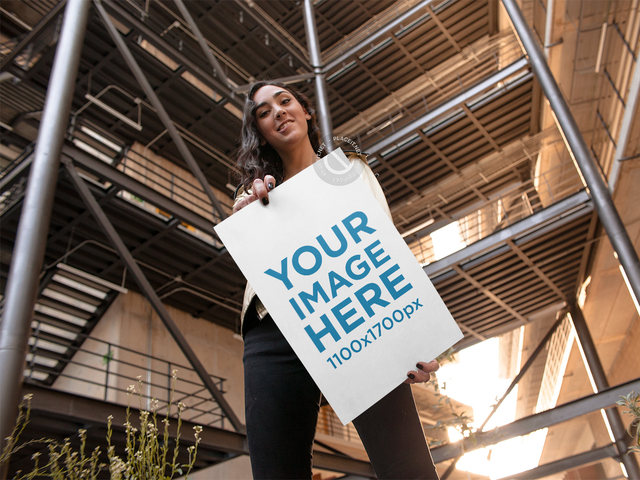 Young Woman Holding a Big Poster While in a Building Mockup a14458