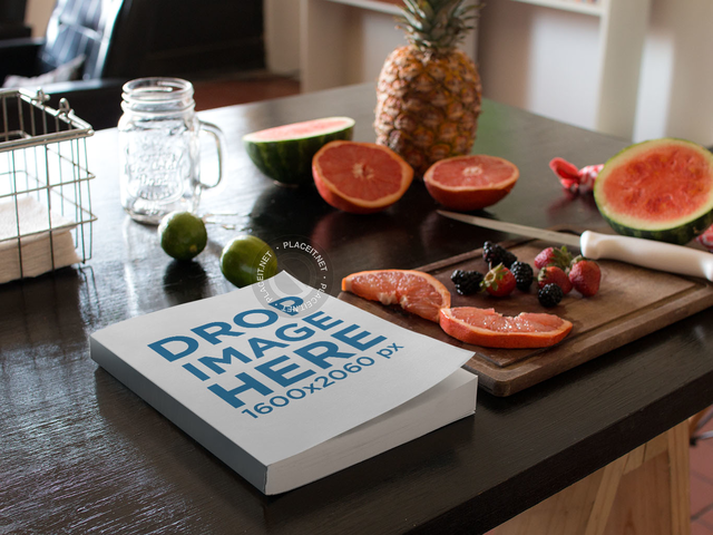 Book Lying On A Kitchen Table Next To Fruits And Knife Mockup A14439