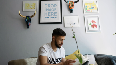 Video Mockup of a Young Hispanic Man Reading a Book in a Living Room With a Framed Art Print on the Wall a14351