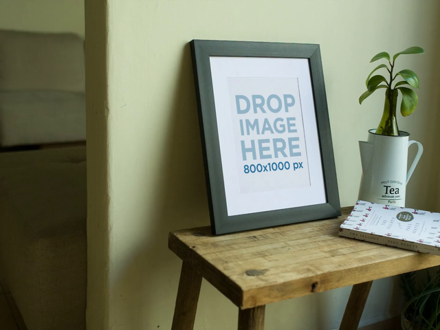 Closeup Video of a Framed Art Print on a Wooden Table With Keys and a Book Nearby a14360