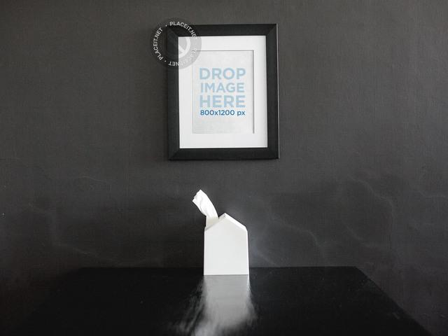 Framed Art Print Mockup On a Black Wall Over a Black Table a14688