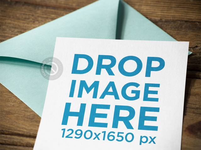 Close Up of an Invitation Template Lying Above a Light Green Envelope on a Wooden Surface a14714