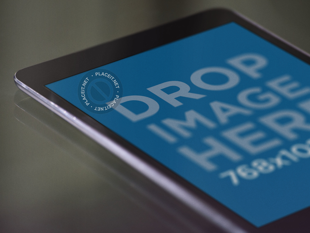 Close Up Mockup of an Angled Black iPad Mini Lying Over a Glass Table a12762