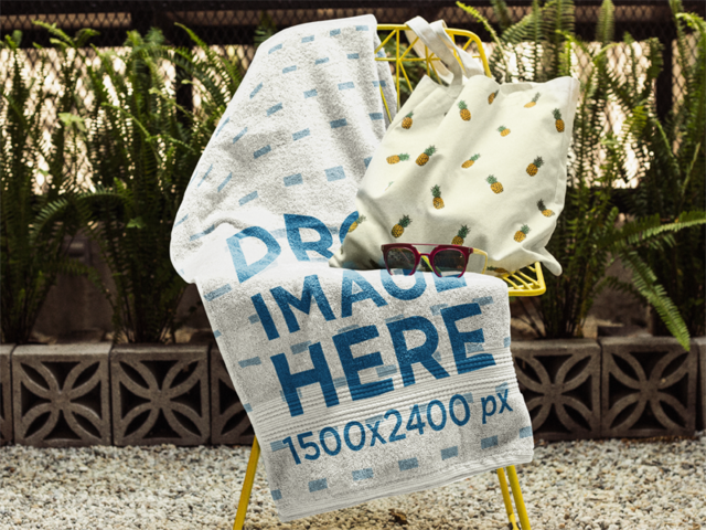 Towel Mockup on a Chair With a Pineapple Printed Bag and Sunglasses Lying on it a14899