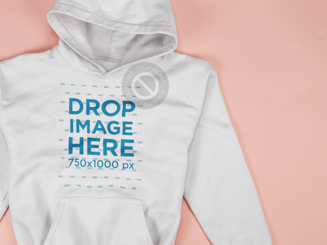 Closeup Mockup of a Pullover Hoodie Lying on a Pink Surface a15243