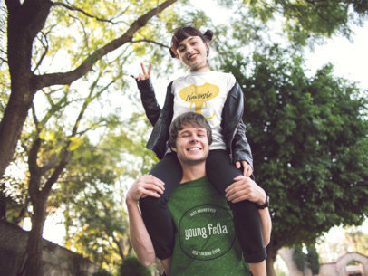 Young Couple Wearing Different T-Shirts Mockup While Playing in the Park a15462