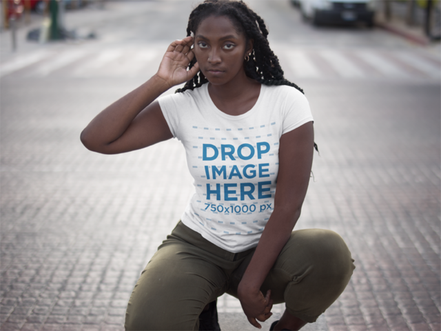 Squatting Black Girl Wearing a Tshirt Mockup While in the Street a15546