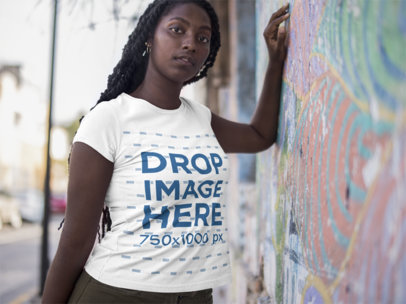 Black Girl Lying Against a Colorful Wall Wearing a Round Neck Tee Mockup a15558