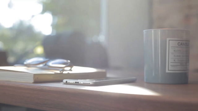 App Demo Video of a White iPhone Lying on a Wooden Table Near a Candle a15459