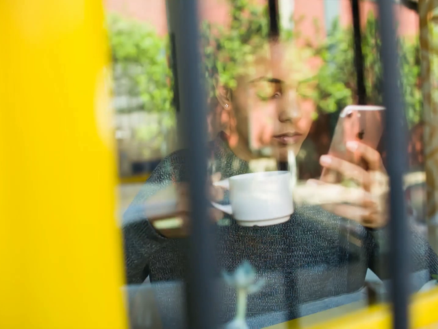 Young Black Girl Having a Coffee by the Window While Checking a Facebook Ad on her iPhone 7 Video a14969