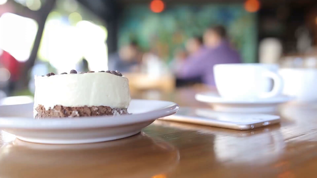 Top Shot of a White iPhone 6 App Demo Video Lying on a Wooden Table Near a Cappuccino and a Cake a158590