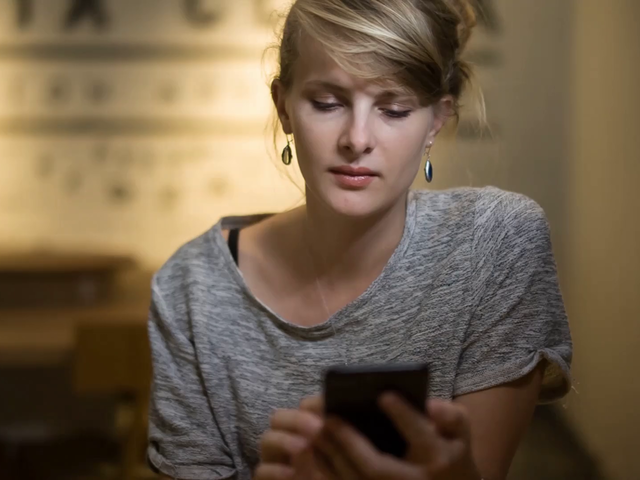 Beautiful Girl Using her iPhone 7 Video Mockup While Sitting Down Indoors a15575