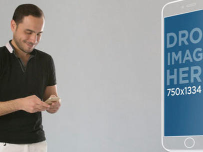Man Using his iPhone 6 Over Gray Backdrop and Large Screenshot