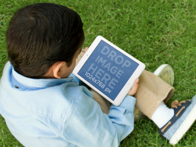 Mockup Template of a Young Boy Using an iPad While at the Garden