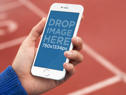 Mockup of a Young Man at a Track Field Using an iPhone 6 a4244