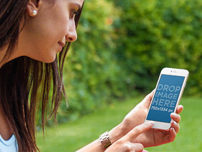 Mockup of a Young Woman Using an iPhone 6 at a Beautiful Garden a4442