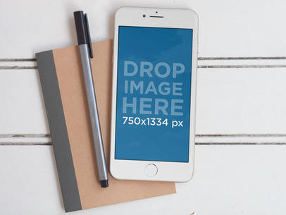 Mockup Featuring a White iPhone 6 Lying on Top of a Notebook a5493