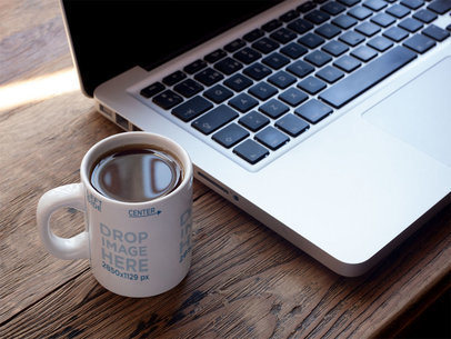 Mockup of a Coffee Cup Sitting Next to a Macbook Pro a6944