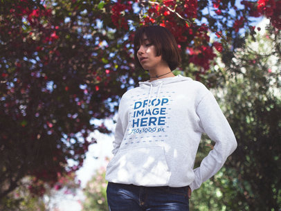 Young Trendy Woman with Short Hair Wearing a Pullover Hoodie Mockup Out in a Flower Grove a12653