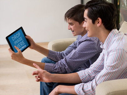 Black iPad Mini Mockup Featuring Two Young Boys Playing in Their Living Room a13061
