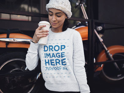 Young Woman with a Beanie and Heather Crewneck Mockup Having a Coffee in the Cold a13173