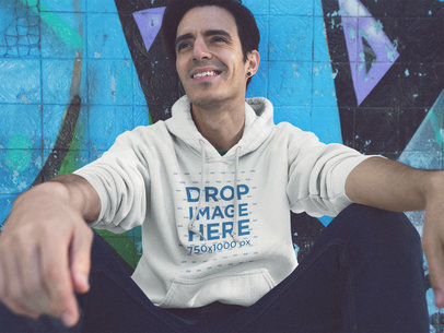 Pullover Hoodie Mockup of a Young Man Sitting and Having Fun at a Skate Park a12838