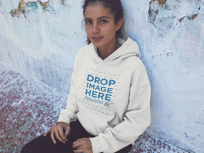 Hoodie Mockup of a Pretty Young Woman Sitting Against an Old Wall a12846
