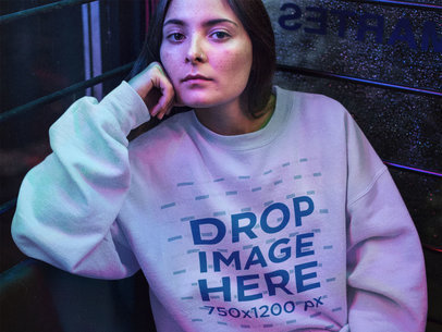 Pretty Young Woman Sitting in a Diner at Night Wearing a Crewneck Sweatshirt Mockup a12685