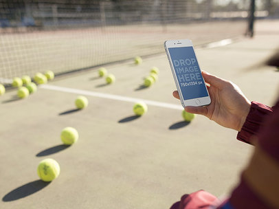 Girl Holding An iPhone While At A Tennis Court Mockup a14092