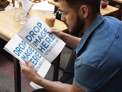 Mockup of a Young Man With Beard Reading a Magazine While at a Coffee Shop a14444