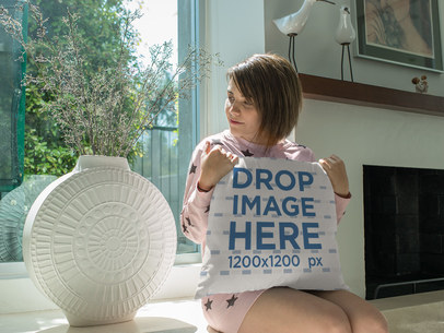Young Girl Looking at a Plant While Holding a Square Pillow Mockup Sitting Down a14933