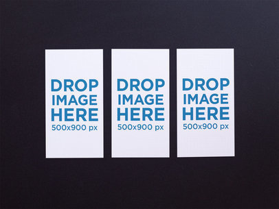 Three Vertical Business Cards Mockup Lying on a Black Surface a15001