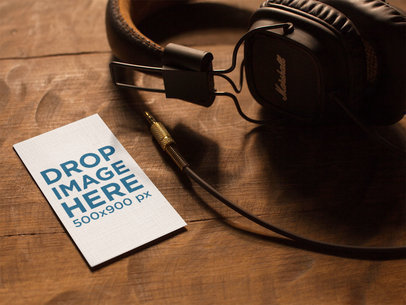 Vertical Business Card Template Lying on a Wooden Table Next to Headphones a14994
