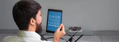 Tablet Mockup of a Man Holding a Black iPad Mini