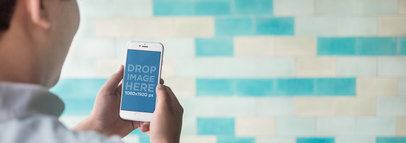 Man Holding an iPhone Over a Blue Tiled Wall Mockup Template