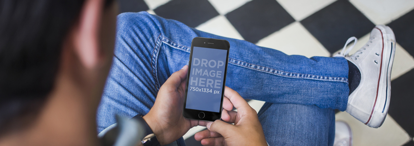 Mockup of a Young Man Holding a Black iPhone 6 Placeit Stage Image