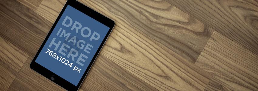 Tablet Mockup of a Black iPad Lying on Hardwood Floor